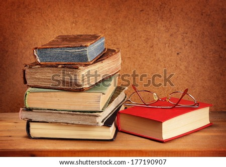 Books stack and glasses on wooden table - stock photo