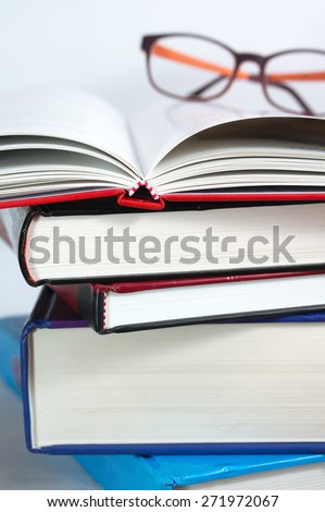 Books stack with open book and reading glasses - stock photo