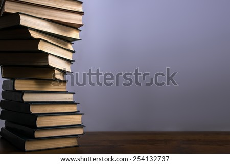 Books stacking. Back to school background. Purple wall. - stock photo