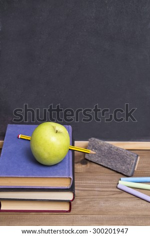 books with apple, eraser and chalk - stock photo