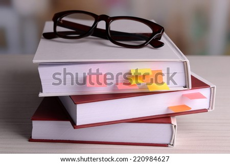 Books with bookmarks and glasses on table on bright background - stock photo