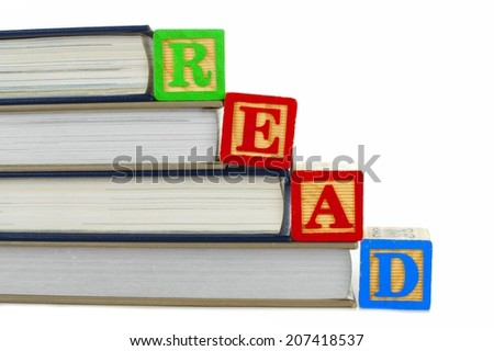 Books with toy wooden blocks spelling READ over white - stock photo