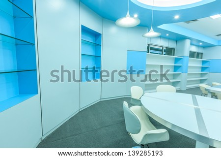 bookshelf and white chair and table in empty modern library - stock photo