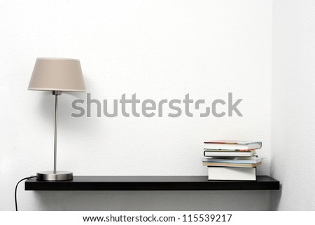 bookshelf on the wall with lamp and books - stock photo