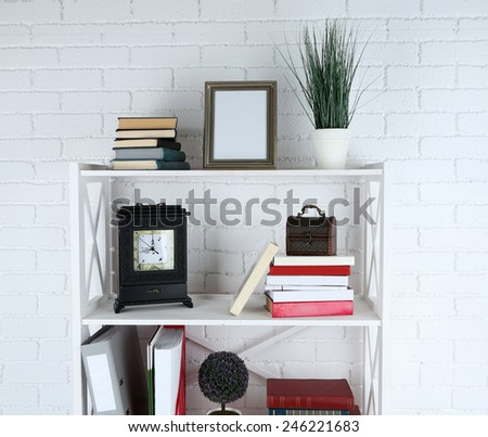 Bookshelves with books and decorative objects on brick wall background - stock photo