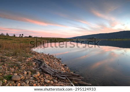 Boorooberongal Lake in Penrith with wispy cirrus clouds turning pink as the sun slips behind the Blue Mountains just before sunset. - stock photo