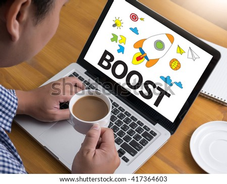 Boost Businessman at work. Close-up top view of man working on laptop while sitting at the wooden desk , coffee - stock photo