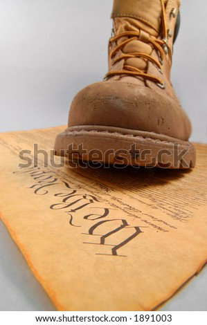 Boot of oppression stepping on the U.S. Constitution - stock photo