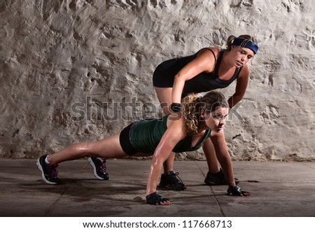 Bootcamp workout coach helps woman with push ups - stock photo