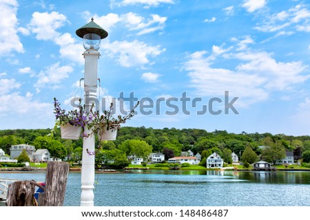 Boothbay, Maine waterfront on a sunny summer day with a wooden lamppost and hanging flower baskets in the foreground. The area is a popular destination for tourists  - stock photo