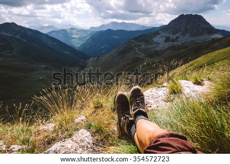 Boots traveler in the mountains. Legs and mountain views - stock photo