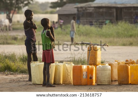 BOR, SOUTH SUDAN-NOVEMBER 1 2013: Unidentified children wait for the water to turn on at a central water point in Bor, South Sudan - stock photo