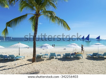 BORACAY, PHILIPPINES - MAY 5, 2015: Tourists on tropical beach. Boracay is one of the main tourist attractions in the philippines because of its white beaches - stock photo