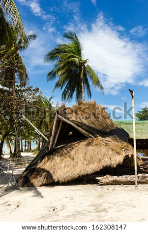 BORACAY, PHILIPPINES - NOVEMBER 9 2013: A roof and building completely destroyed by Typhoon Haiyan rests next to a beach.  Super Typhoon Yolanda caused devastation over large parts of the Philippines - stock photo