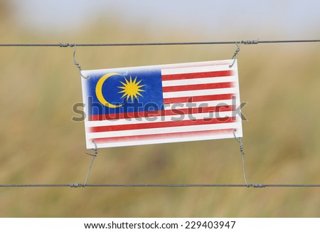 Border fence - Old plastic sign with a flag - Malaysia - stock photo