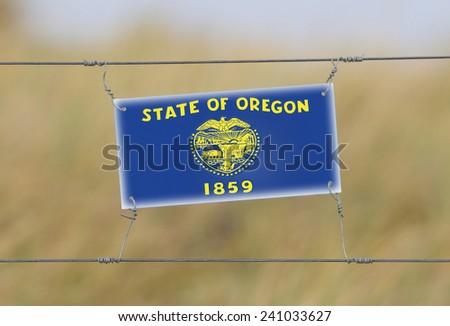 Border fence - Old plastic sign with a flag - Oregon - stock photo