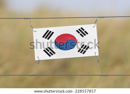Border fence - Old plastic sign with a flag - South Korea - stock photo