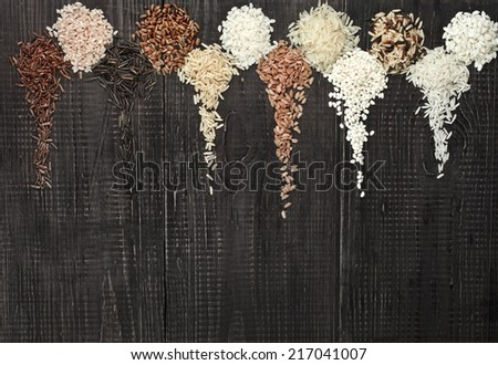 Border Frame made of colorful blend several varieties grain rice heap in a rustic wooden surface background - stock photo