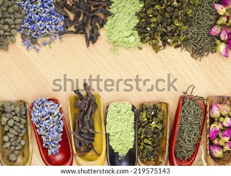 border frame of different dry tea addition  in scoops on wooden table background, top view - stock photo