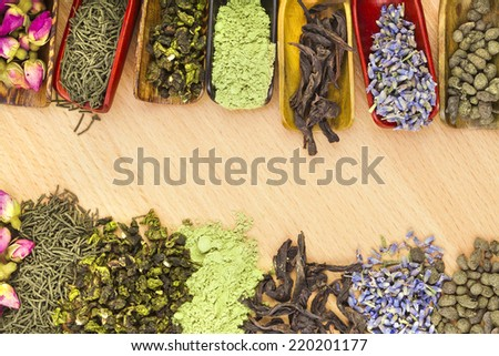 border frame of different heap dry tea on wooden table background, top view - stock photo