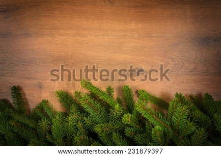 border from green fir branches on wooden deck - stock photo