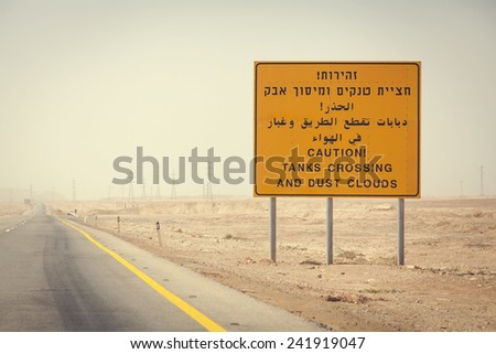Border Guard Warning indicating tanks crossing and dust clouds on the road in the Israel desert - stock photo
