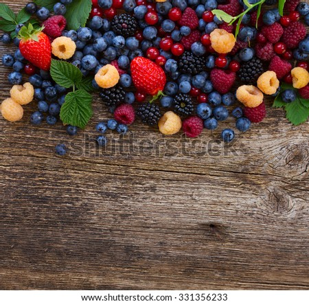 border of fresh  berries mix on wooden tabletop with copy space - stock photo
