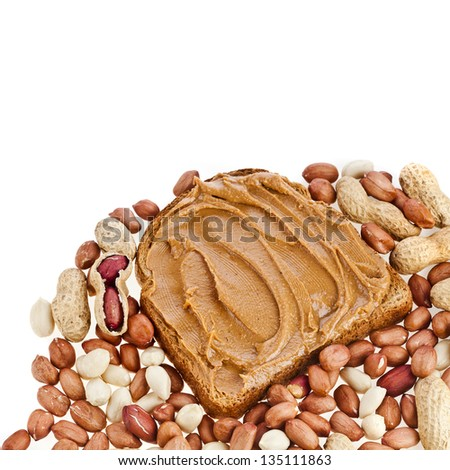 border of peanut butter sandwich and peanuts on white background - stock photo