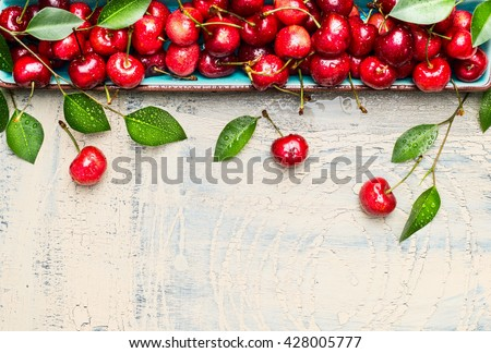 Border of sweet cherries with green leaves on light wooden background, top view, place for text. Summer fruits and berries concept. - stock photo