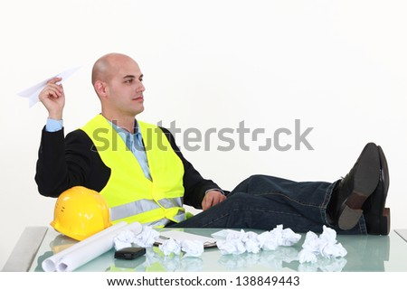 Bored architect making paper planes at his desk - stock photo