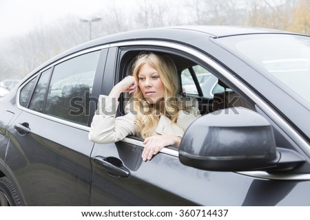 Bored attractive young woman sitting waiting in a car staring out through the open window with a glum expression - stock photo