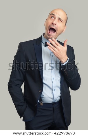bored bald stylish man yawning and looking up. Gray background - stock photo