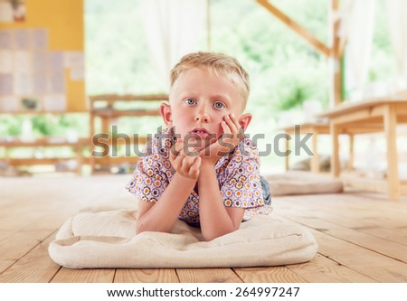 Bored boy lying on the wooden terrace on summer day - stock photo