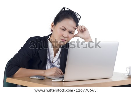 Bored business woman working on laptop looking very boring at the computer, Isolated white background. Model is Asian woman. - stock photo