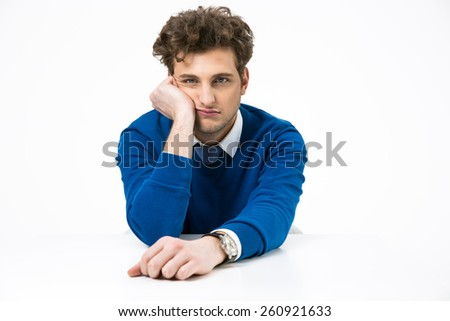 Bored businessman sitting at the table over white background - stock photo