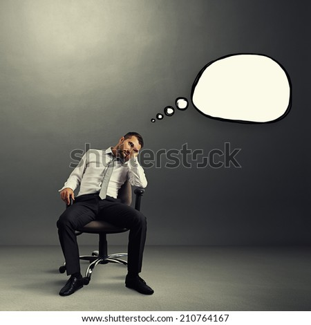 bored businessman sitting on the chair with empty speech bubble over grey background - stock photo