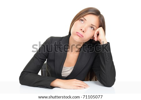 Bored businesspeople: woman sitting at desk staring bored upwards. Beautiful young multiethnic asian caucasian business woman isolated on white background. - stock photo