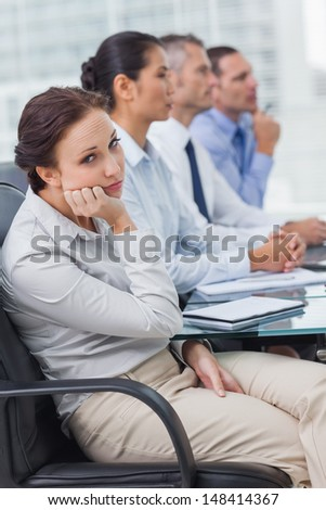 Bored businesswoman looking at camera while attending presentation in bright office - stock photo