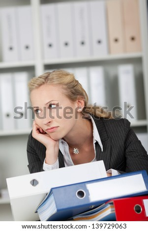 Bored businesswoman with stack of binders in office - stock photo