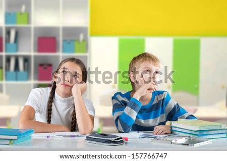 Bored children sitting by the table and looking away - stock photo