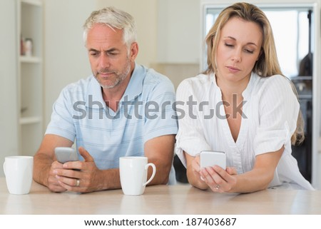 Bored couple sitting at the counter texting at home in the kitchen - stock photo