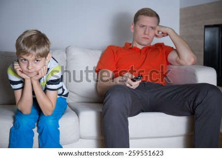 Bored little son sitting with his father in living room - stock photo