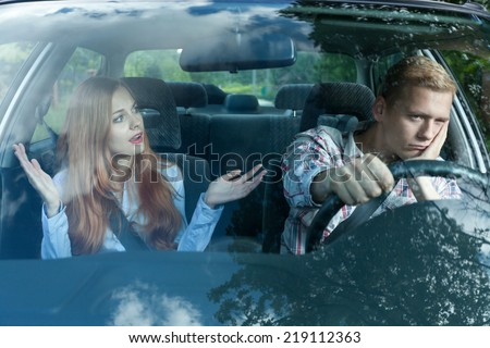 Bored man in a car listening to wife - stock photo