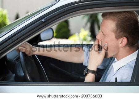 Bored man in car waiting in traffic jam - stock photo