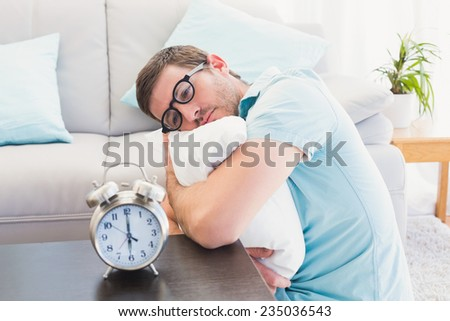 Bored man on the table beside alarm clock hugging a pillow at home in the living room - stock photo