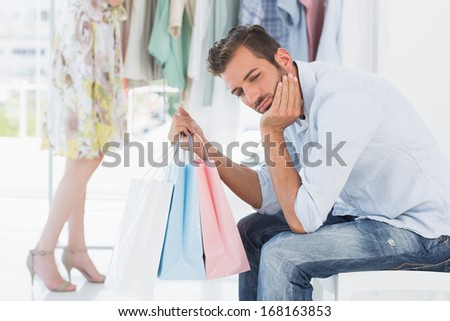 Bored man sitting with shopping bags while woman by clothes rack in the background - stock photo