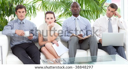 Bored multi-ethnic business people in a waiting room - stock photo