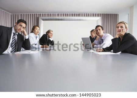 Bored multiethnic business people sitting in conference room - stock photo