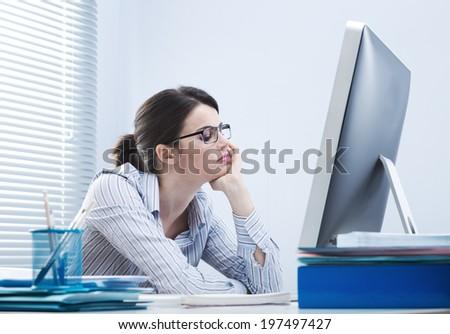 Bored office worker at desk staring at computer screen with hand on chin. - stock photo