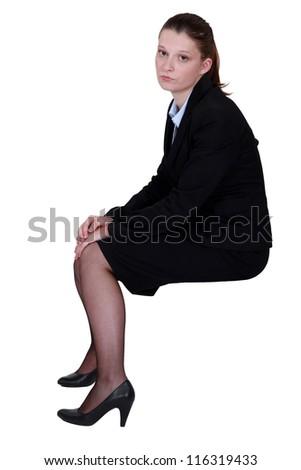 Bored office worker sat on stool - stock photo